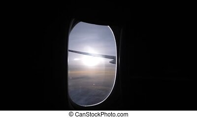 bright sun over horizon view from plane dark cabin porthole