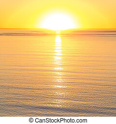 Bright sun reflected in the calm water at sunset