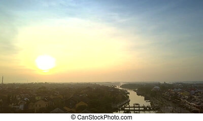 bright sun rises above dark city with river - tremendous...