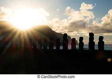 Bright sun rising behind Moai silhouettes in Easter Island -...