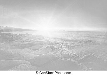 Bright sunlight over rocky coastal area in black and white.