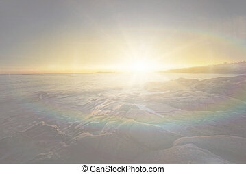 Bright sunlight over rocky coastal area with rainbow colors