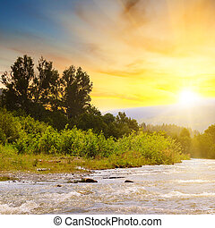 Bright sunrise in the mountains of the Carpathians, Ukraine. The rays of the sun are reflected in the mountain river.