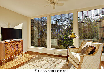 Bright sunroom with antique chair and tv