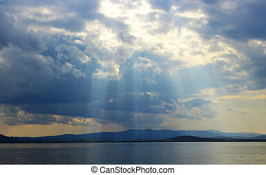 Bright sun's rays passing through the storm clouds over the lake
