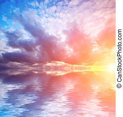 bright sunset and dramatic clouds with sun at calm sea backgroun