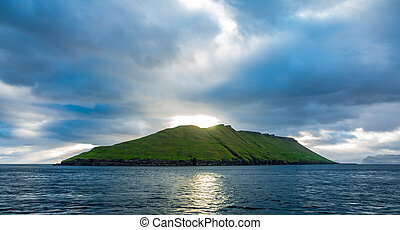 Bright sunset over isolated island with cloudy sky