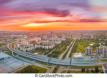 Bright sunset over the city c with highway and bridge, aerial view from a height.