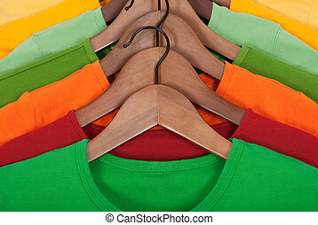 Bright t-shirts on wooden hangers