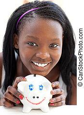 Bright teen girl holding a piggy-bank