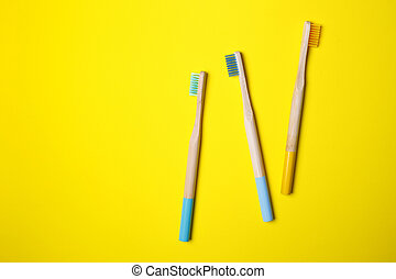 bright toothbrushes on a yellow background