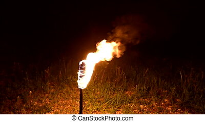 Bright torch stands on ground burning at night. Close-up. ...
