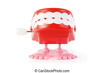 bright toy clockwork jaw with white teeth on pink legs on white background