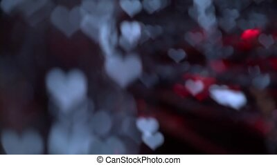 Bright twinkling lights against in the shape of a heart on a black screen. Bokeh background