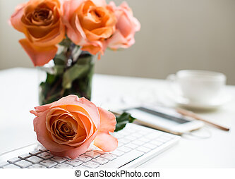 Bright white office table decor with fresh flowers, computer keyboard and smart phone. Woman's modern workspace, interior details.