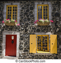 Bright Window Frames against a Historic Stone Building in Quebec City