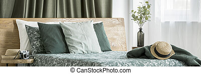 Straw hat lying on dark green blanket near bright window with olive drapes in natural bedroom interior
