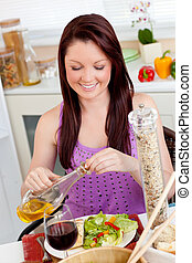 Bright woman eating a salad with oil in the kitchen