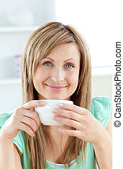Bright woman holding a cup of coffee in the kitchen