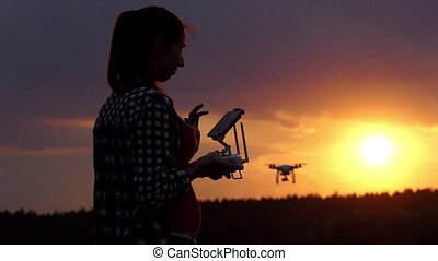 Bright woman holds a panel to operate her drone at sunset in slo-mo