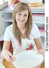 Bright woman preparing a cake in the kitchen