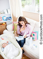 Bright woman sitting on the sofa with bags reading a card while her baby is sleeping in his cradle at home