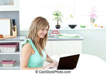 Bright woman using her laptop in the kitchen