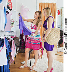 Bright women choosing clothes together