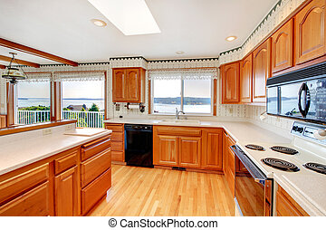 Bright wood cozy kitchen with water view and white...