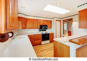 Bright wood cozy kitchen with water view and white countertop.