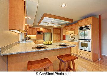 Bright wooden kitchen interior with skylight and steel appliances. Northwest, USA