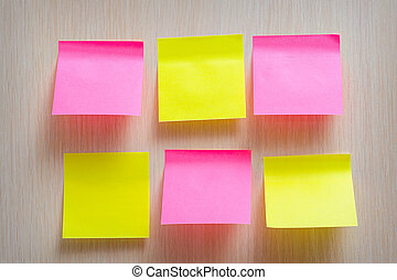 bright yellow and pink stickers on a wooden background