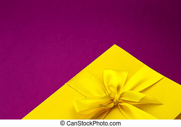 Bright yellow giftbox on dark pink background