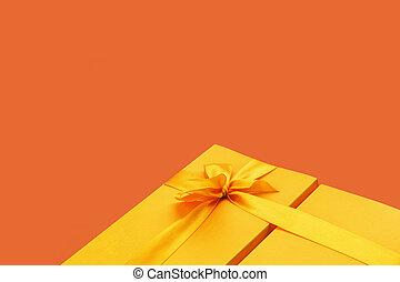 Bright yellow giftbox on dark saffron orange background