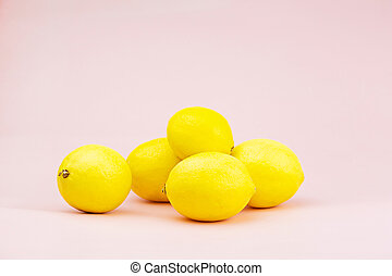 Bright yellow lemons on a pink background