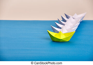 Bright yellow paper ship leading white ones based on blue ...