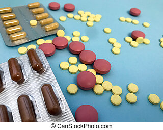 bright yellow, red and brown pills on a blue background, poured out of the package. medical background for flat. scattered medicine for letters. stylization of drugs