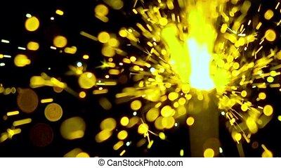 Bright yellow sparkler against dark background. Super slow...