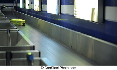 Bright yellow suitcase is traveling on conveyor belt in airport.