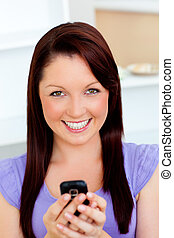 Bright young woman sending a text looking at the camera