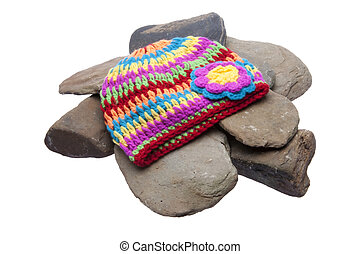 Brightly colored hat sits on a pile of smooth rover rocks. Isolated on a white background with a clipping path.