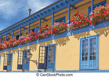 brightly colored house with balcony full of flowers
