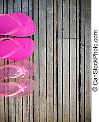 Brightly colored pink flip-flops of a mother and daughter on wood. Family vacation