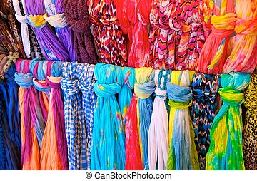 Brightly Colored Scarves on Rack - Two rows of brightly...