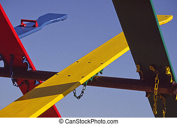 Brightly colored see-saws form a pleasing abstract pattern at a playground.