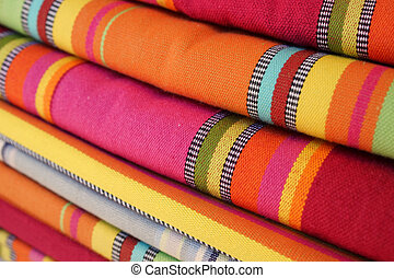 Brightly colored textiles in the market - A stack of...