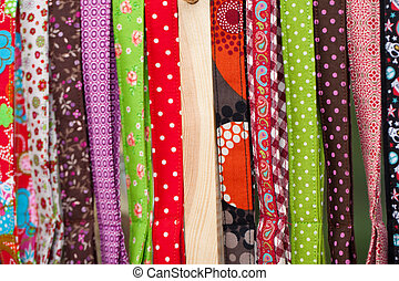 Brightly coloured textiles folded neatly and stacked upright for use in producing colourful modern clothing