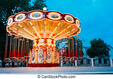 Brightly Illuminated Empty Carousel Merry-Go-Round. Nobody In Summer Evening In City Amusement Park.