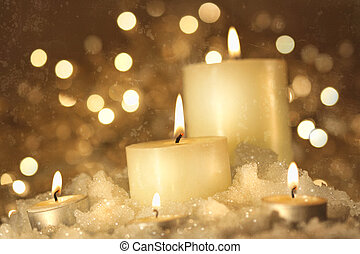Brightly lit candles in wet snow against sparkly background