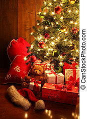 Brightly lit Christmas tree with gifts - Closeup of brightly...